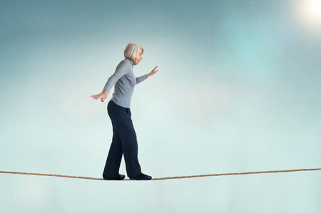 Foto de senior woman walking on a tightrope - Imagen libre de derechos