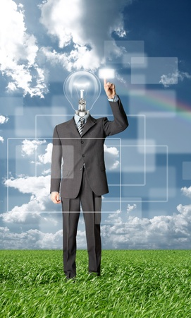 full length businessman with lamp-head push the button on virtual touch pad outdoors