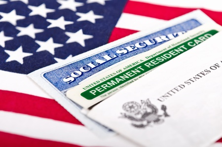 United States of America social security and green card with US flag on the background  Immigration concept  Closeup with shallow depth of field