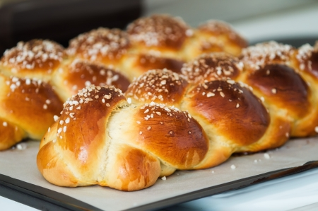 Freshly baked sweet braided bread loaf on a baking sheet, shallow depth of field