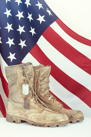 Photo pour Old combat boots and dog tags with American flag in the background - image libre de droit