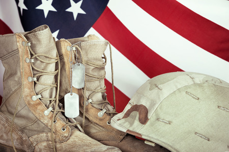 Old combat boots, dog tags, and helmet with American flag in the background, closeup