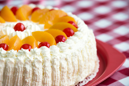 Photo pour Homemade cream cake with peaches and cherries, closeup with shallow depth of field - image libre de droit