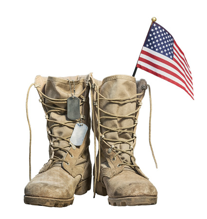 Old military combat boots with the American flag and dog tags