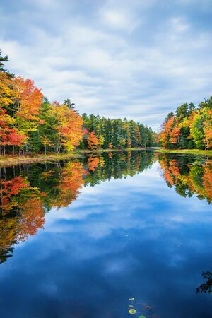 Foto de Fall foliage colors reflected in still lake water on a beautiful autumn day in New England - Imagen libre de derechos