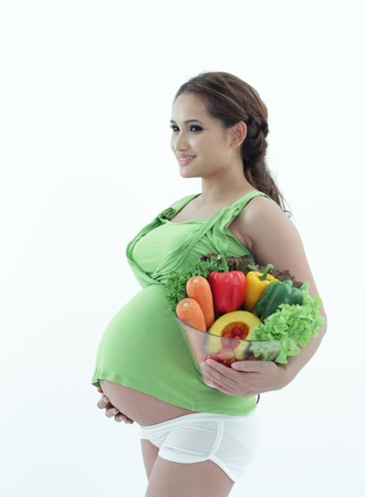 Pregnant woman holding a bowl of salad.