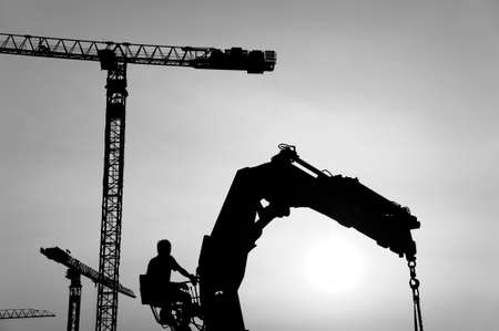 Photo for silhouette of crane and worker in construction site - Royalty Free Image