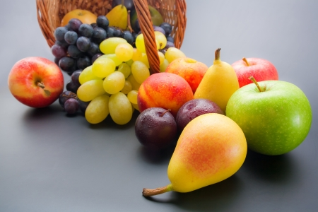 Various fresh ripe fruits close-up: plums, peaches, pears, apples and grapes scattered from wicker basket on neutral gradient background