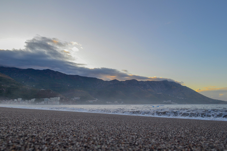 Sea view. Early morning. The sun rises. The sea calms down after a night storm. Water dust. Montenegro. Budva