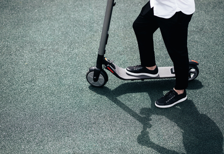 Photo pour Legs of a man in stylish outfit stand on electric scooter on the street - image libre de droit