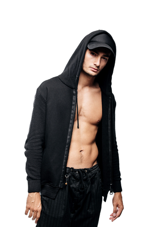 Foto de Handsome  young dancer dressed in black pants, a sweatshirt on a naked torso and a hood on the cap stands on a white background - Imagen libre de derechos