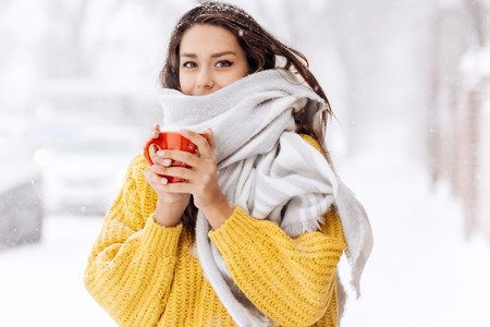 Foto de Nice dark-haired girl in a yellow sweater and a white scarf standing with a red mug on a snowy street on a winter day - Imagen libre de derechos