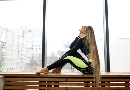 Foto de Beautiful athletic girl with very long blond hair is sitting on the wooden windowsill next to the panoramic windows in the gym - Imagen libre de derechos