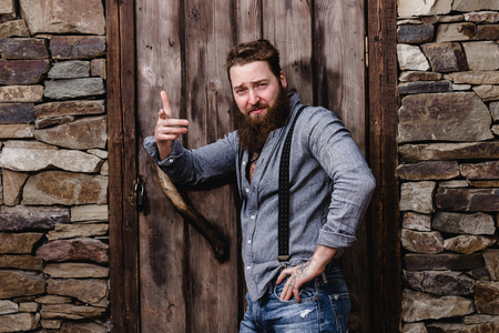 Photo for Strong brutal man with a beard and tattoos on his hands dressed in stylish casual clothes poses on the background of stone wall and wooden door - Royalty Free Image