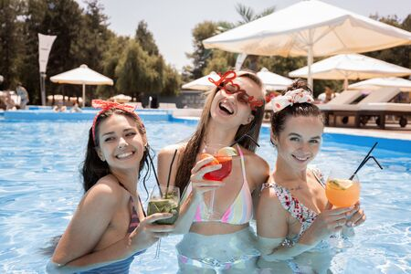 Photo pour Tree young slim girls in the swimsuits are relaxing and drinking cocktails in the swimming pool next to lounge zone on the open air on a sunny summer day - image libre de droit