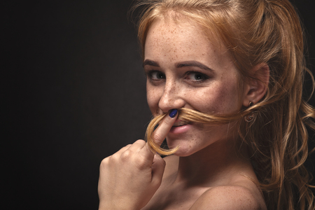 fun young woman making mustache from her hair