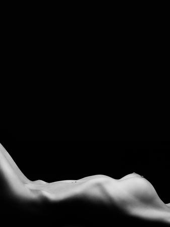 Photo pour naked tan female body lying on black background, monochrome image with copyspace - image libre de droit