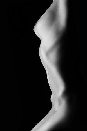 Photo pour naked tan female body on black background, monochrome image - image libre de droit
