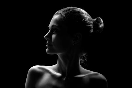 Photo pour beautiful female profile with bare shoulders on black background, monochrome - image libre de droit