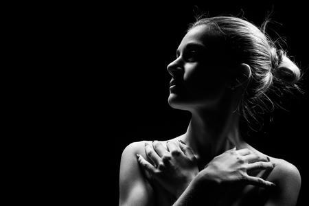 Photo pour beautiful female profile with bare shoulders on black background with copy space, monochrome - image libre de droit