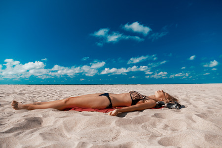 single topless young woman in swimsuit at sand sea beach with blue sky and clouds tanning lying