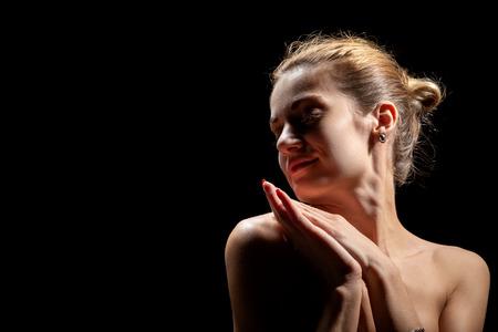Photo pour beautiful female profile with bare shoulders on black background with copy space - image libre de droit
