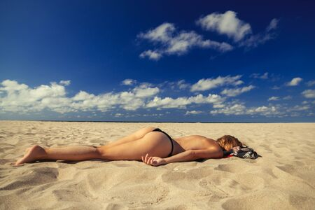 young blond woman tanning on sand sea beach under sun rays