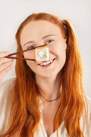 Photo for fun girl with sushi roll on white background smiling looking at camera show nose - Royalty Free Image
