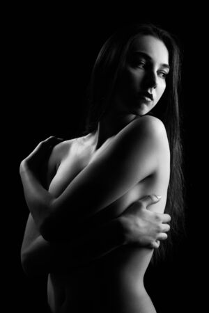 Photo pour topless sensual woman on black background embraced herself, looking aside, monochrome - image libre de droit