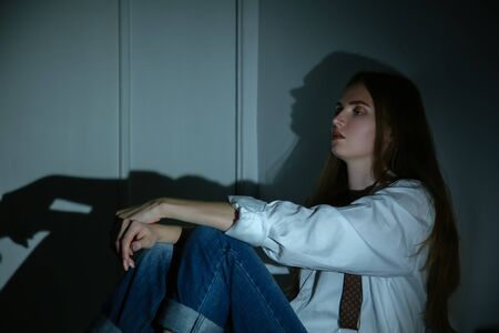 Photo pour sad young woman sitting in dark in corner looking ahead profile view - image libre de droit