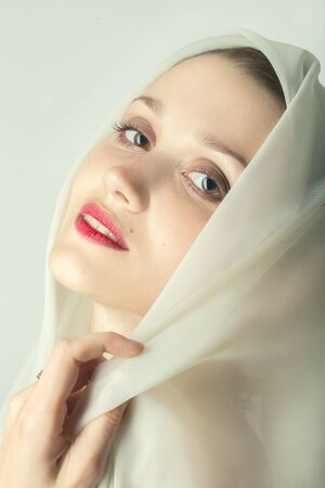 Photo pour beautiful young woman with eastern makeup cover her head with white veil on white background, looking at camera, smiling - image libre de droit