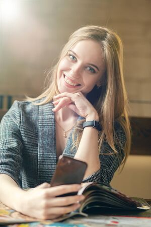 Photo pour happy blond young woman with mobile phone sitting with magazines and booklets, making shoot, looking at camera, smiling - image libre de droit