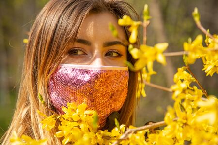Photo pour serious young woman with black medical protective mask at spring flowers looks at camera - image libre de droit