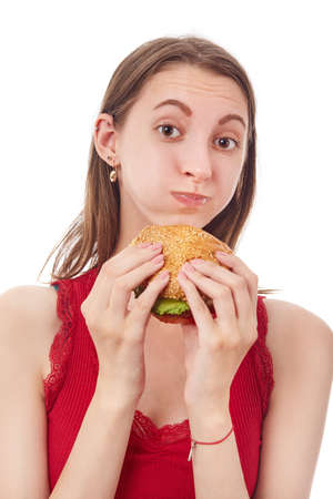 Photo for happy young woman eats cheeseburger on white background isolated looking at camera smiling - Royalty Free Image
