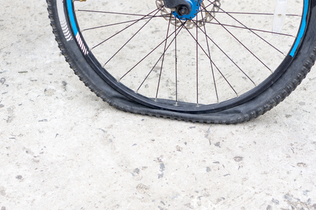 Photo pour Closeup view of bicycle flat tire on pavement. - image libre de droit