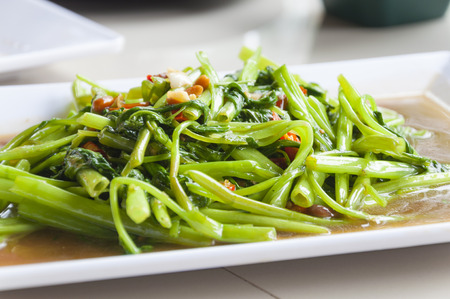 Stir Fried Water Spinachon white plate, Thai food