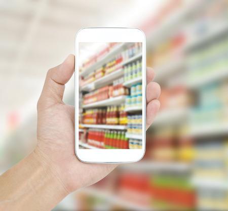 Hand holding mobile on Supermarket blur background