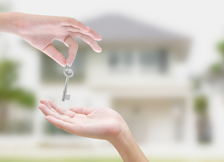 Hand holding key on white background