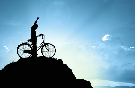 Photo pour Man and bicycle on mountain in the sunlight - image libre de droit