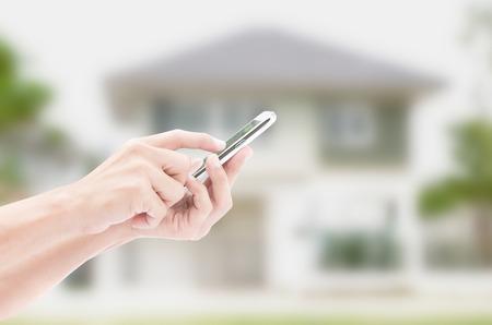 Photo pour Hand holding smart phone on house backgrounds - image libre de droit