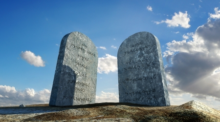 Ten commandments stones viewed from ground level in dramatic perspective with sky and clou