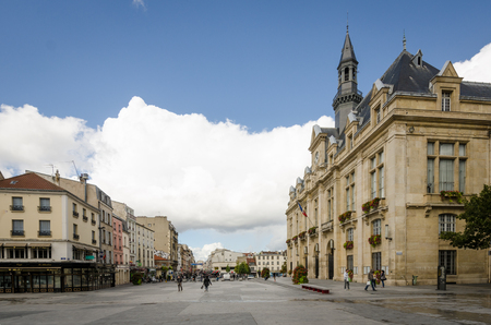 SAINT-DENIS - FRANCE, SEPTEMBER 14, 2015: People are walking in front of the City Hall of Saint-Denis, which overlooks Place Victor Hugo with Rue de la Republique in the distance. Saint-Denis is a suburb of the French capital.
