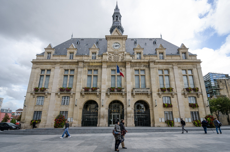 Saint-Denis, France, September 14, 2015 - A man with his luggage stands in front of the City Hall of Saint-Denis, which overlooks Place Victor Hugo.