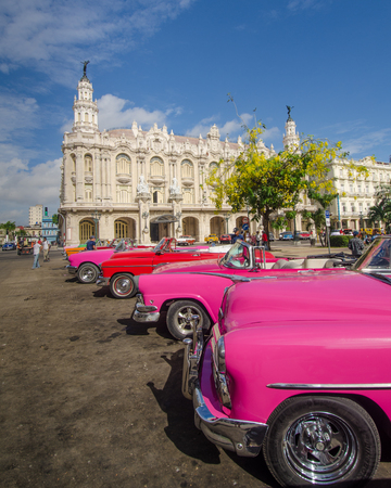 HAVANA - CUBA, JUNE 10, 2016: Close-up of restored classic convertibles waiting for passengers with the Great Theater (Gran Teatro de La Habana) in the background.