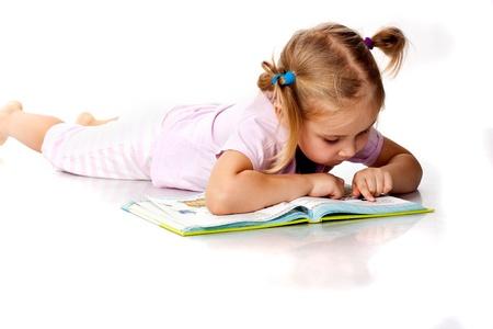 Beautiful girl lying reading a book