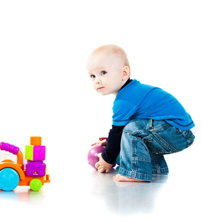 Photo pour Baby boy playing with the ball isolated on white - image libre de droit