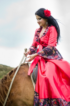 Beautiful gypsy girl riding a horse in the fieldの写真素材