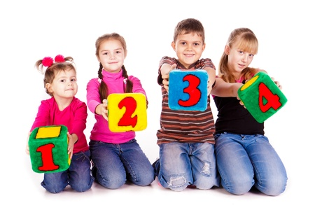 Happy kids holding blocks with numbers over white background