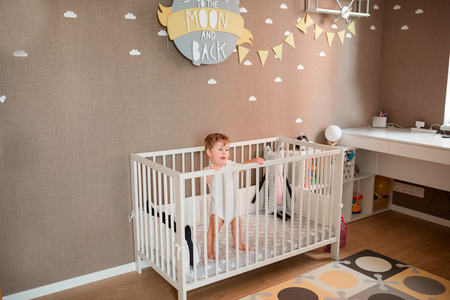 Photo for Cute little baby boy looking out of his bed in his room - Royalty Free Image