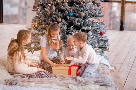Photo for Happy kids having fun and opening presents near christmas tree. - Royalty Free Image